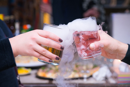 Beautiful couple holding dry ice cocktails at the party. Purple cocktail drink with ice vapor at the club, celebration