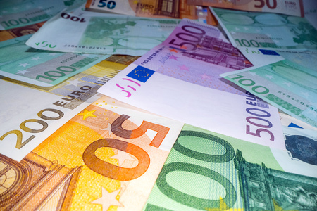 Wide angle view of euro notes background stacked on top of each other. Euro money banknotes, pile of money, cash, stack of bills. Investing money, savings