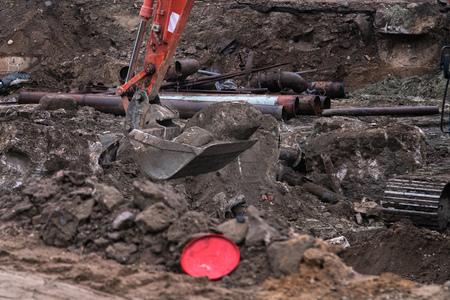 Big industrial excavator digging up ground, urban development. Bulldozer scoop working in construction site