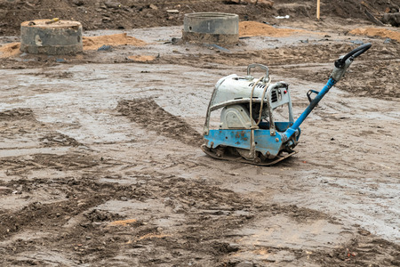 Plate compactor on the ground at construction site. Vibratory hammer power tool, jumping jack machine compressing ground