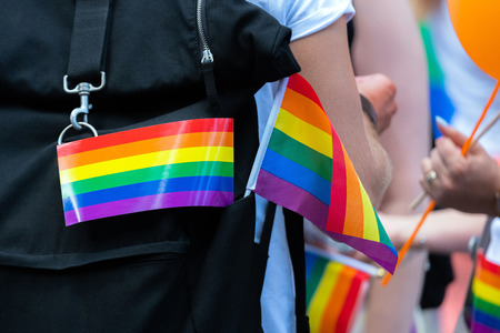 Little rainbow flag supporting LGBT community on gay parade event. Colourful flag on backpack during gay pride celebration Stock Photo