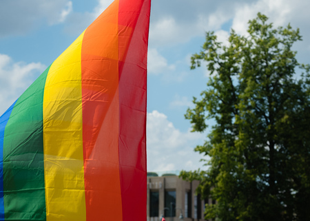 Rainbow flag supporting LGBT community on gay parade event. Colourful flag in the crowd during gay pride celebration Stock Photo - 124898876
