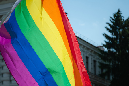 Rainbow flag supporting LGBT community on gay parade event. Colourful flag in the crowd during gay pride celebration Stock Photo - 124898920