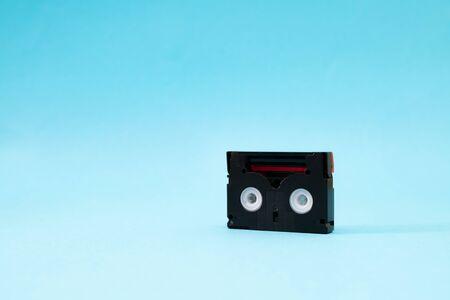 Vintage mini DV cassette tape used for recording video back in a day. Plastic, magnetic, analog film tape on blue background Banco de Imagens - 124898998