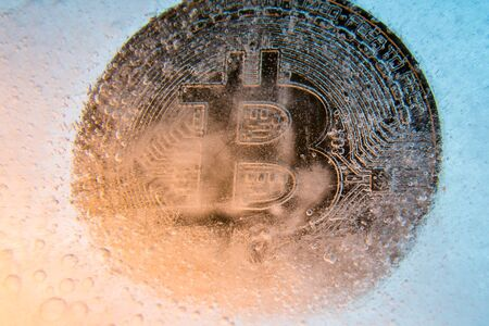 Silver Bitcoin, bit coin online digital currency frozen in the blue ice. Concept of block chain, crypto market crash. Frozen crypto money, depreciation Banco de Imagens - 128823143