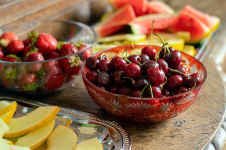 Fresh summer fruits: cherries, organic strawberries, melon slices, water melon in vintage crystal bowl on old wooden table