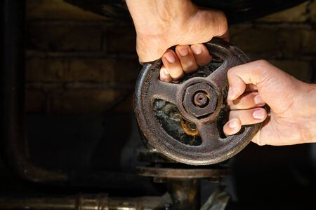 Mans hands trying to turn rusty valve on boiler room pipes. Old metal boiler generating heating and delivering it to home through pipeline Banco de Imagens