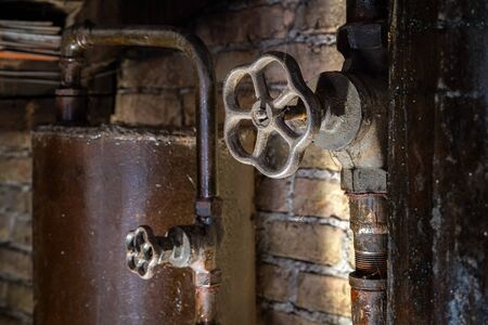 Rusty boiler room pipes. Old metal boiler generating heating and delivering it to home through pipeline. Hot water or gas is being delivered with this system