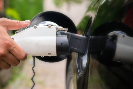 Mans hand inserting charger plug into electric car in green environment background. New energy vehicle, NEV is being loaded with electricity power. Ecology, modern day cars