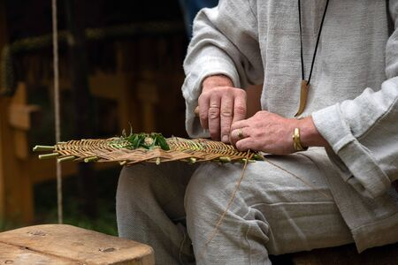 Close up of craftsman wearing rural clothes making wicker basket of twigs. Traditional handmade weaving technique at rural village