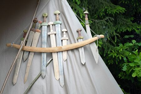 Wooden medieval weapons replicas for close combat displayed on grey fabric texture Banco de Imagens