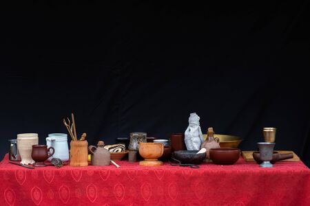 A lot of clay cups, pots, plates, vases and other dishes on top of table with red tablecloth and black background