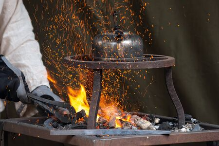 Blacksmith heating up metal in red hot coals while tea pot boiling water on top. Craftsman hand forging metal, red sparks are rising up
