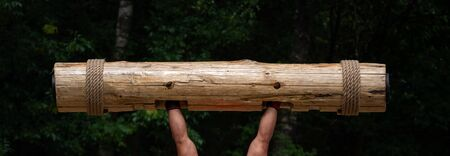 Strongest man in the world competition. Muscular hands lifting up heavy wooden trunk. Giant, mighty man lifting wood log at competition Banco de Imagens