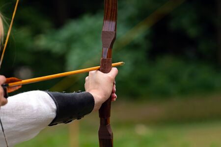 Archer holds his bow aiming at the target. Archery competition, outdoor activity