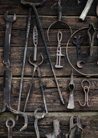 Rustic rural tools used by ancestors in the village in agriculture, carpentry, by blacksmiths. Ancient work tools on vintage wooden background