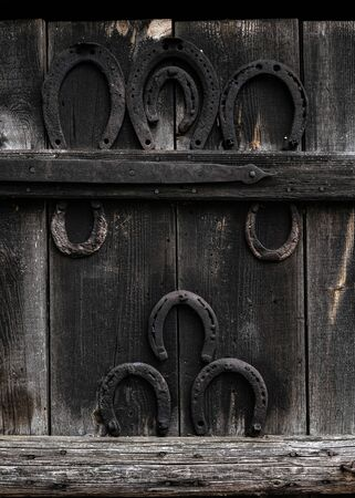 Rustic horseshoe on vintage wooden background. Old horse shoe hanging on wooden door in the village - symbol of luck