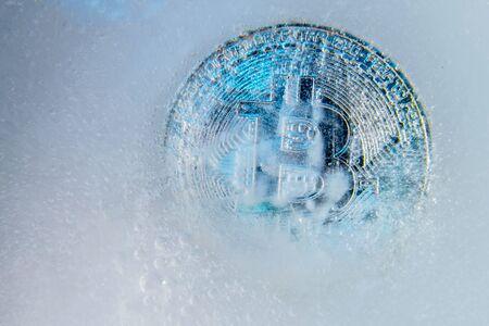 Silver Bitcoin, bit coin online digital currency frozen in the blue ice. Concept of block chain, crypto market crash. Frozen crypto money, depreciation Banco de Imagens