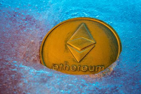 Golden Ethereum coin, online digital currency frozen in the blue ice. Concept of block chain, market crash. Frozen crypto money, depreciation