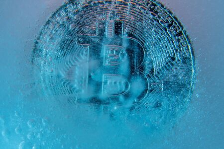 Silver Bitcoin, bit coin online digital currency frozen in the blue ice. Concept of block chain, crypto market crash. Frozen crypto money, depreciation Banco de Imagens - 128823207