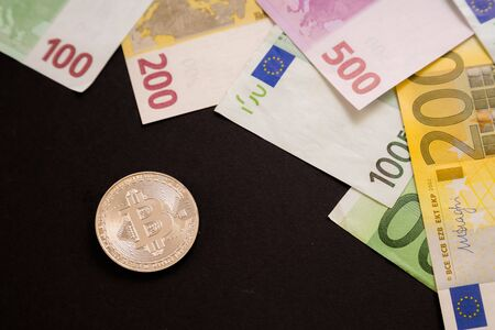 Silver Bitcoin coin next to Euro bank notes on black background. Digital currency, block chain market. Euro bills next to crypto coin