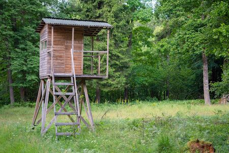 Hunters hut in the forest by the road. Hunter tower or watch post in the wilderness. Hunter post is a wooden structure to watch and shoot at wild animals Stok Fotoğraf