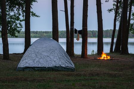 View of the campsite by the lake at twilight. Tent and burning fire place by the water surrounded by trees in the forest. Spending the night in wilderness