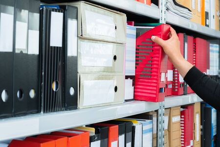 Mans hand picking a blank blind folder with files from the shelf. Archival, stacks of documents at the office or library