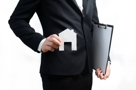Realtor, real estate agent holding tablet and paper model of a house. Getting access to home. Investment and buying property concept