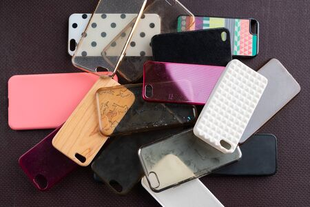 Pile of multicolored plastic back covers for mobile phone on dark background. Choice of smart phone protector accessories background. A lot of silicone phone backs or skins next to each other