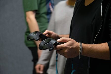 Young man playing virtual reality game while wearing headset and holding controller game pad in hands