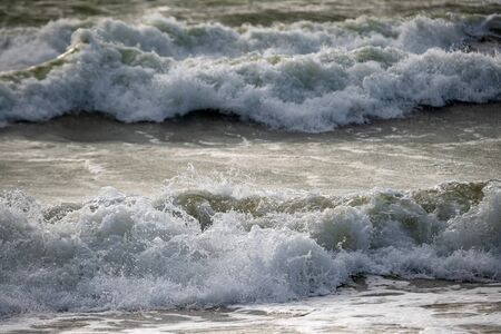 Breaking waves in the sea. Dangerous ocean waves with foam crashing near the beach, upcoming tide Stockfoto