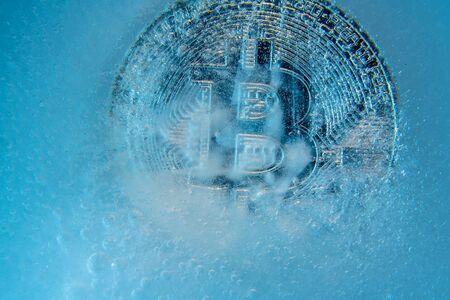 Silver Bitcoin, bit coin online digital currency frozen in the blue ice. Concept of block chain, crypto market crash. Frozen crypto money, depreciation Foto de archivo