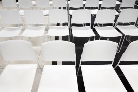 Rows of white plastic chairs for formal meetings, conference, lectures, graduation ceremonies. Room full of empty white chairs.