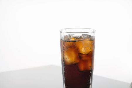 Cold refreshing cola glass with ice on white background with space for text. Icy beverage of cool drink with caffeine