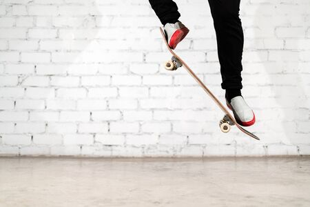 Skateboarder performing skateboard trick - ollie on concrete. athlete practicing jump, preparing for competition. Extreme sport, youth culture, urban sport