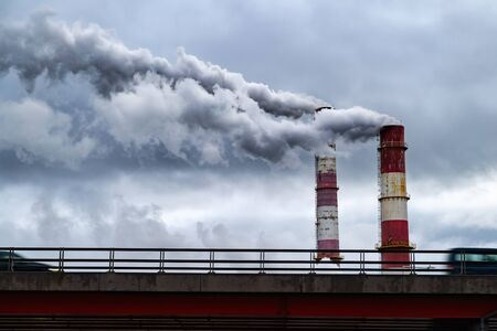 Dark toxic smoke clouds coming out of factory chimney above car traffic. Air pollution and global warming caused by old industrial power plant