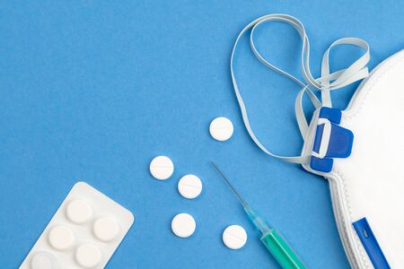 Still life of medical objects - flu vaccine, pills and needle on blue background. Corona virus, covid-19 treatment