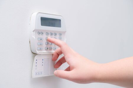 Woman hand entering alarm system password of an apartment, house of business office. Surveillance and protection console against rubbery and thief