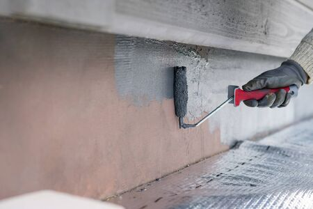 Man painting home socle with paint roller. Close up of rolling grey paint on building plinth. Home renovation Banco de Imagens
