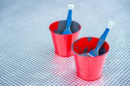 Close up of paint brushes in paint buckets outside. Home renovation