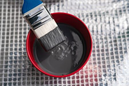 Paint brush and a bucket with paint still life. Painting house outside. Home renovation. Nobody