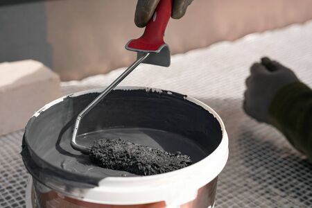 Close up of paint roller dipping into grey paint outside. Home renovation.