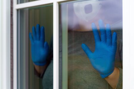 Women hand with medical gloves next to the window indoor. Home isolation. Corona virus. Stay at home.