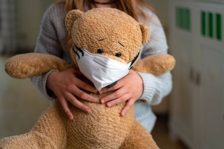 Teenage girl hugging teddy bear with face mask. Concept of corona virus, staying at home, isolation. Preventing flu virus
