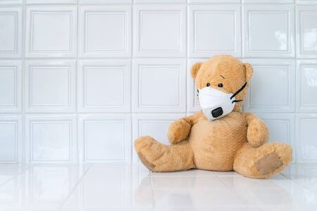 Teddy bear with face mask on white background. Concept of home school, isolation. Staying at home. Corona virus.