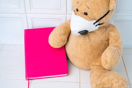 Teddy bear with face mask and pink note book on white background. Concept of home school, isolation. Staying at home. Corona virus. Banco de Imagens