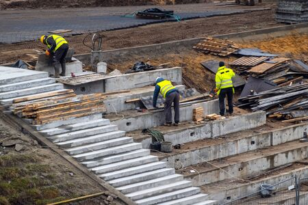 Builders working on construction foundation. Man strengthen concrete structure on the hill slope