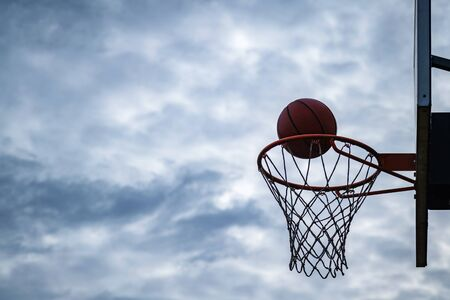 Dark silhouette of street basketball ball falling into the hoop on a cloudy day. Close up of a ball above the hoop net. Concept of success, scoring points and winning. Urban youth game.