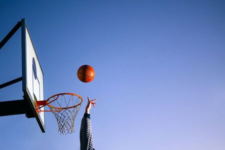 Street basketball ball player throwing ball into the hoop. Close up of hand, orange ball above the hoop net with blue sky in the background. Concept of success, scoring points and winning. Copy space